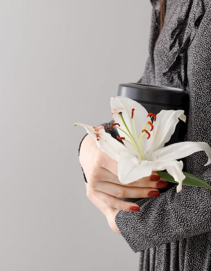woman in grey coat holding a white lily
